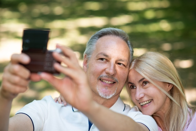 Ritratto di una coppia matura che scatta un autoritratto in un parco