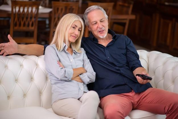 Ritratto di una coppia matura che guarda la televisione