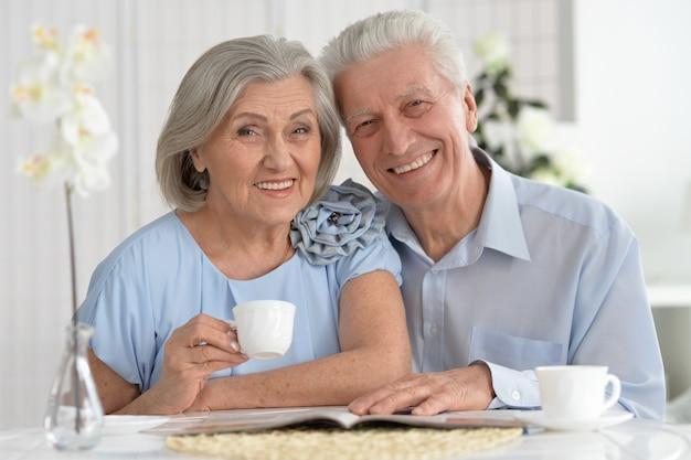 Ritratto di coppia matura con rivista che beve tè
