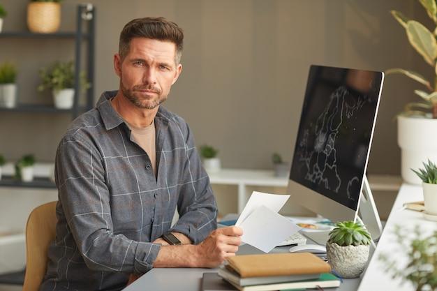 Ritratto di designer maturo guardando davanti mentre si lavora al suo posto di lavoro in ufficio