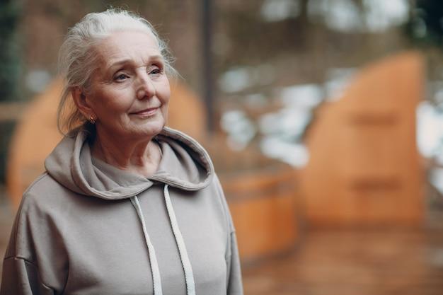 Ritratto di donna anziana dai capelli grigi matura in felpa con cappuccio all'aperto