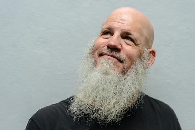 Ritratto di uomo maturo bello calvo hipster con barba lunga contro il muro di cemento