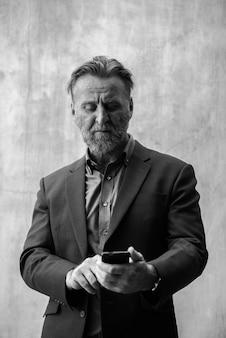 Ritratto di uomo d'affari barbuto bello maturo con capelli biondi in tuta contro il muro di cemento all'aperto in bianco e nero