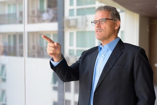 Ritratto dell'uomo d'affari bello maturo dalla finestra di vetro