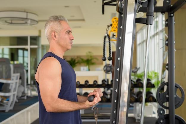 Ritratto di un bell'uomo persiano maturo con i capelli grigi che si esercita in palestra