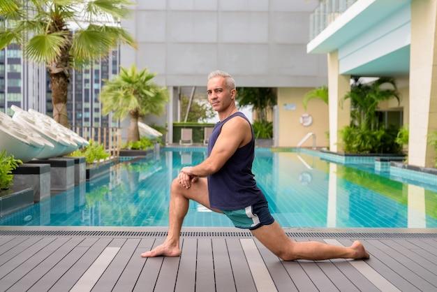 Ritratto di un bell'uomo persiano maturo con i capelli grigi che si rilassa in piscina sul tetto