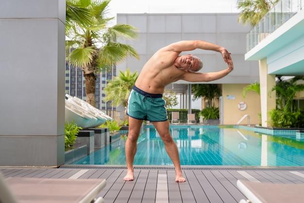 Ritratto di un bell'uomo persiano maturo con i capelli grigi a torso nudo in piscina sul tetto