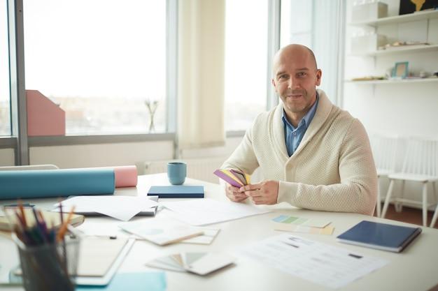 Ritratto del progettista maschio maturo che sorride e che tiene i campioni di colore mentre posa sul posto di lavoro, spazio della copia