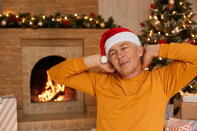 Ritratto di uomo maturo prima di natale, seduto vicino al camino e albero di natale e allungando le mani, sembra assonnato, indossa un maglione giallo casual e cappello di babbo natale.