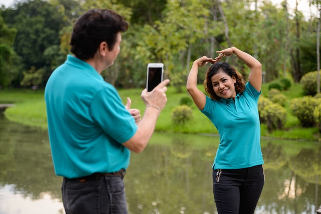 Ritratto di uomo maturo e donna asiatica matura come coppia sposata multietnica insieme e innamorata al parco all'aperto