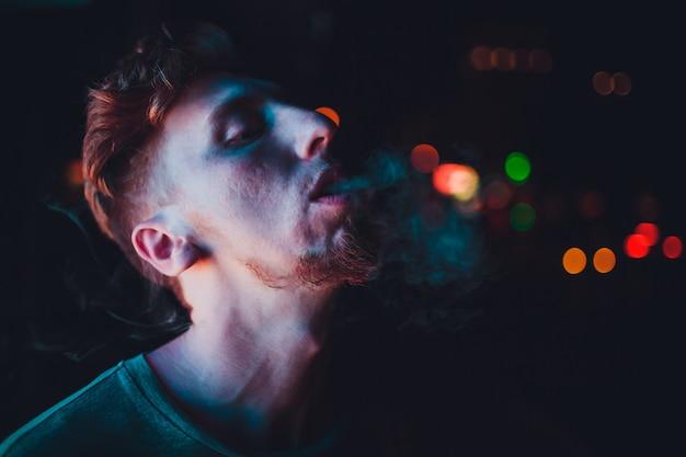 Uomo maturo del ritratto che fuma sigaretta elettronica nelle vie alla notte
