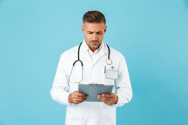 Ritratto di maturo medico con stetoscopio in possesso di tessera sanitaria, in piedi isolato sopra la parete blu