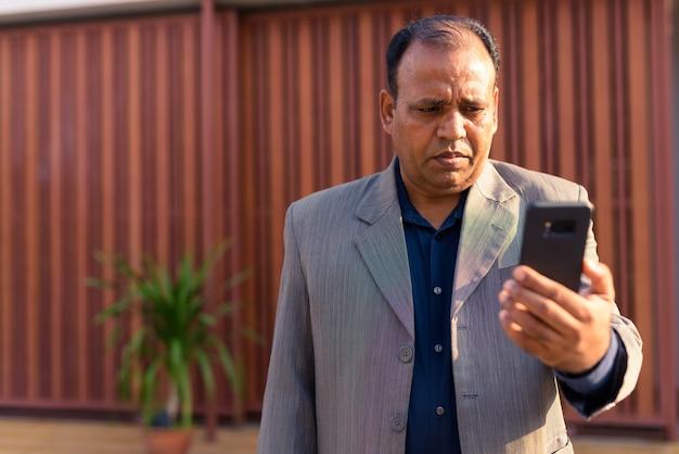 Ritratto di maturo uomo d'affari indiano in sovrappeso con stempiato che indossa tuta in strada