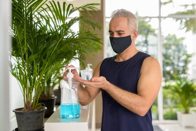 Ritratto di uomo persiano maturo con maschera per la protezione dall'epidemia di virus corona distanza sociale in palestra