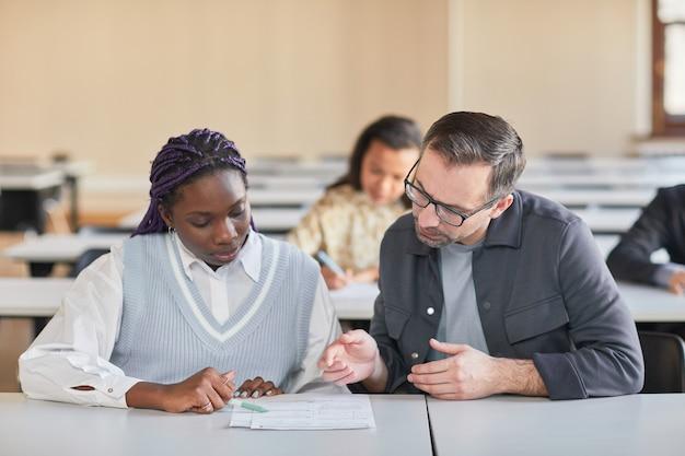 Ritratto di professore maturo che aiuta una donna afroamericana che studia nell'auditorium del college, copia spazio