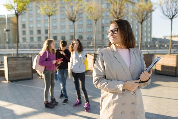 Ritratto dell'insegnante femminile sorridente maturo in vetri con la lavagna per appunti