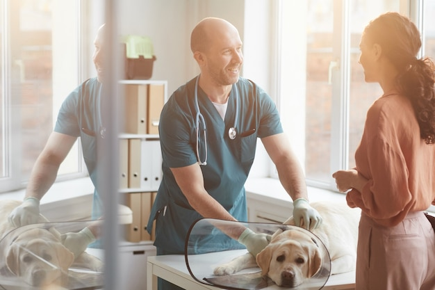 Ritratto di veterinario maturo che esamina cane alla clinica veterinaria e sorride mentre parla con una giovane donna, scena illuminata dalla luce del sole, copia spazio