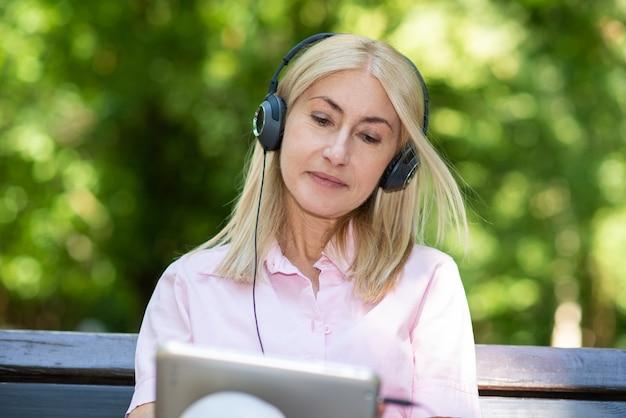Ritratto di una donna matura che ascolta musica all'aperto
