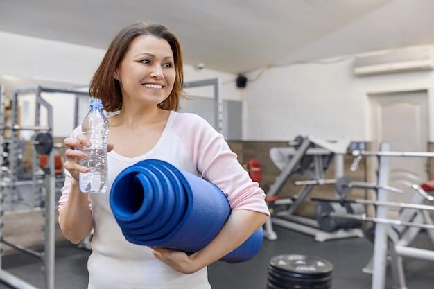 Ritratto della donna matura con la bottiglia di acqua e la stuoia di sport nel centro benessere