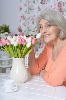 Ritratto di donna matura con fiori che beve tè