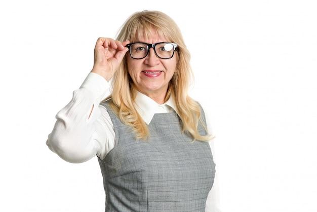 Ritratto di una donna matura con gli occhiali su uno sfondo chiaro. sorriso, emozioni positive.