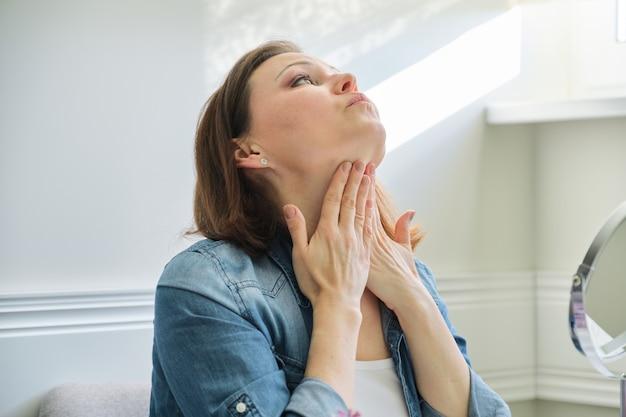 Ritratto di donna matura con specchio per il trucco che massaggia il viso e il collo
