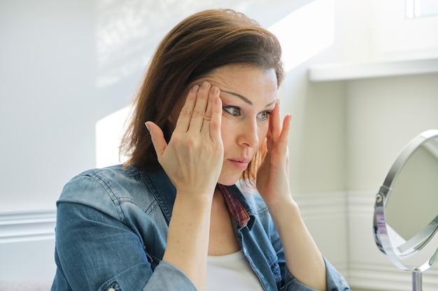 Ritratto di donna matura con specchio cosmetico massaggiando il viso