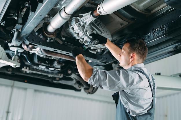 Ritratto di un meccanico che ripara un'auto sollevata.
