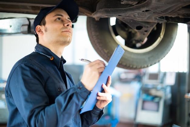 Ritratto di un meccanico che cattura le note mentre ispeziona un'automobile