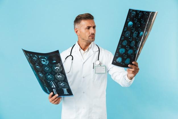 Ritratto del medico 30s con lo stetoscopio che tiene le immagini dei raggi x, in piedi isolato sopra la parete blu