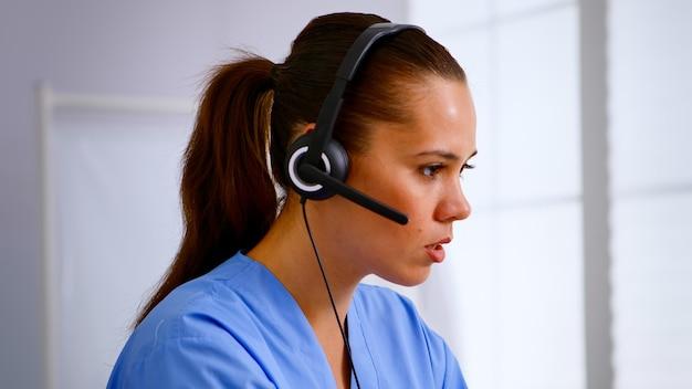 Ritratto di receptionist medico che risponde premendo sulla cuffia aiutando il paziente a fissare un appuntamento in ospedale. medico sanitario in uniforme medica, assistente medico durante la comunicazione di telemedicina