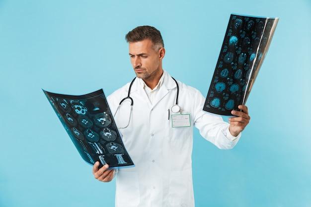 Ritratto di operaio medico anni '30 con lo stetoscopio che tiene le immagini dei raggi x, in piedi isolato sopra la parete blu