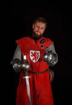 Ritratto di un cavaliere medievale di mezza età con un fiore forgiato, rosa, con la spada di un cavaliere in mano e l'armatura, su una parete scura