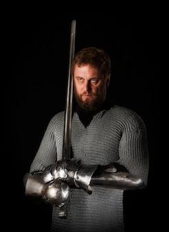 Ritratto di un cavaliere medievale con la barba in cotta di maglia con la spada di un cavaliere in mano e armatura, isolato su una parete scura