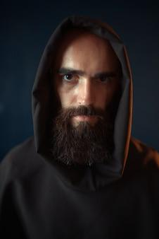 Ritratto di monaco medievale in veste nera con cappuccio, religione. frate misterioso in mantello scuro