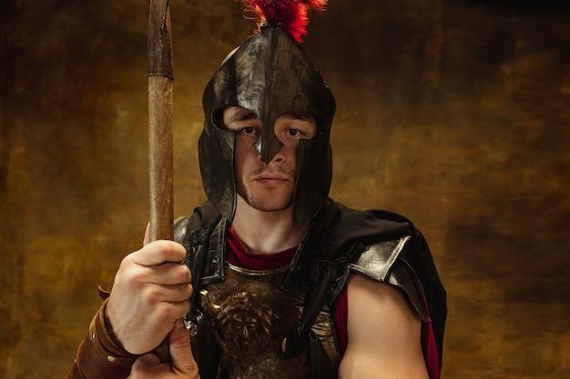 Ritratto di persona medievale, guerriero in equipaggiamento da guerra isolato su sfondo scuro vintage.