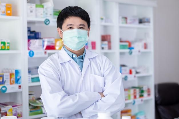 Ritratto di uomini farmacista asiatico in piedi abbraccio e maschera protettiva in farmacia