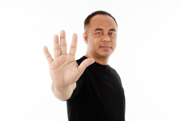Ritratto di un uomo asiatico anziano di mezza età con una maglietta nera che mostra le sue cinque dita per il numero 5 o proibisce, rifiuta il modo. isolare su sfondo bianco.