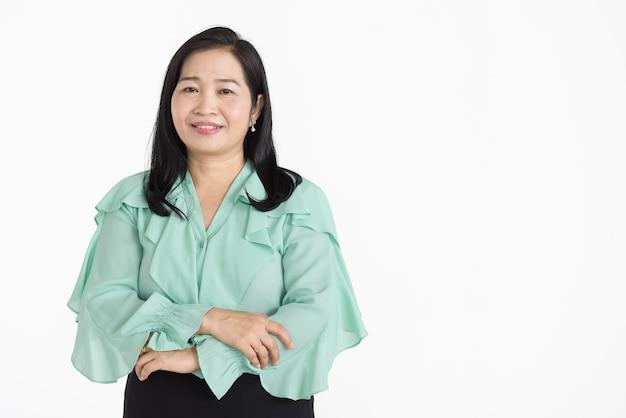 Ritratto di donna asiatica di mezza età che indossa una camicetta verde menta che sembra ordinata sorridendo magnificamente con fiducioso isolato.