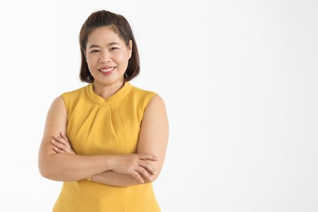 Ritratto di donna asiatica di mezza età che indossa una camicetta gialla che sorride magnificamente con fiducioso isolato.
