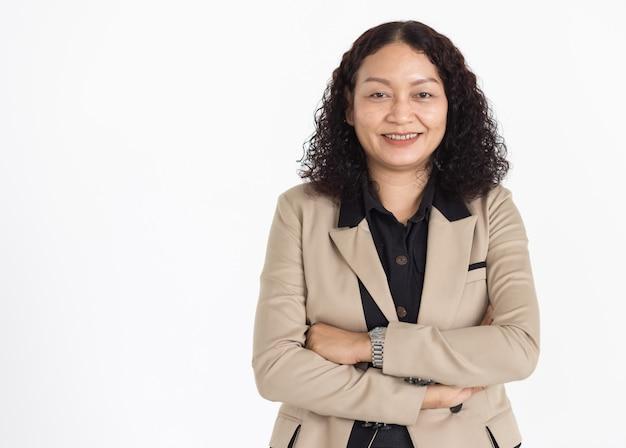 Ritratto di una donna asiatica di mezza età con capelli neri ricci che indossa una camicia nera e una giacca beige che guardano ordinatamente sorridendo con fi