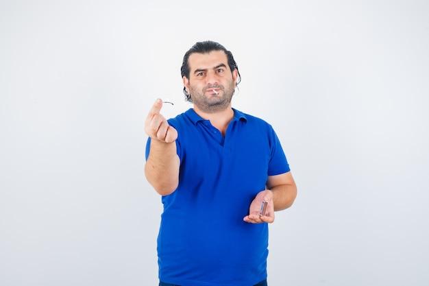 Ritratto di uomo di mezza età fiammiferi di illuminazione in t-shirt polo e guardando pensieroso vista frontale