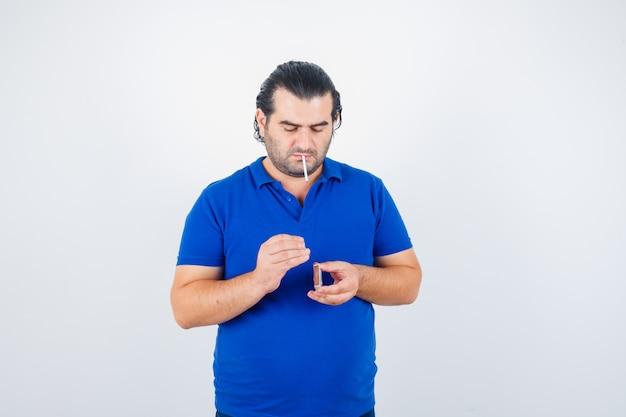 Ritratto di uomo di mezza età cercando di accendere la sigaretta con fiammiferi in t-shirt polo e guardando vista frontale focalizzata