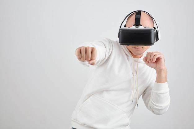 Ritratto di uomo di mezza età con occhiali per realtà virtuale che combatte in un videogioco, isolato su bianco