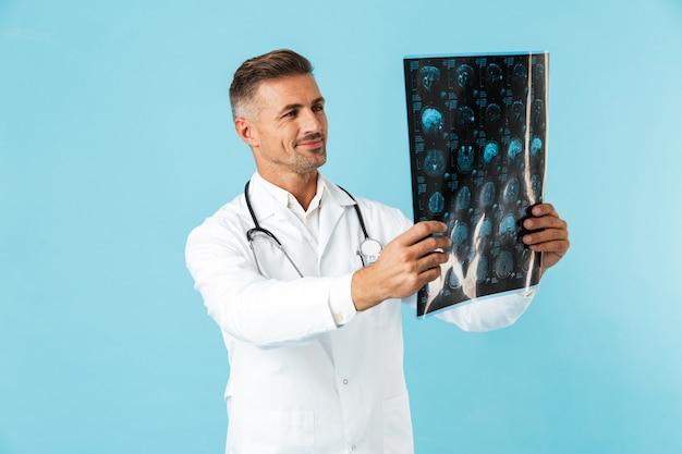 Ritratto del medico di mezza età con lo stetoscopio che tiene l'immagine dei raggi x, in piedi isolato sopra la parete blu