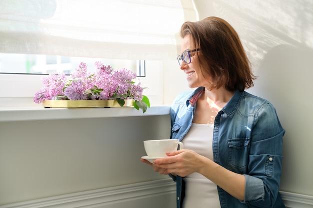 Ritratto di donna di mezza età a casa con fiori, donna sorridente in piedi vicino alla finestra con una tazza di tè e bouquet di lillà, spazio di copia