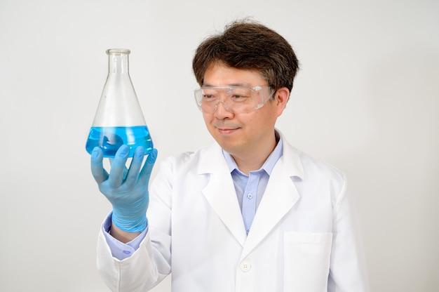 Ritratto di uno scienziato maschio asiatico di metà anno che indossa un abito bianco da laboratorio e guanti e tiene in mano un contenitore sperimentale.