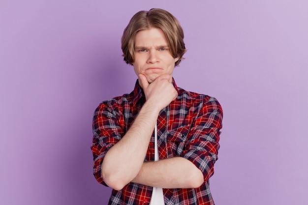 Ritratto di un ragazzo intelligente con le dita che guardano la telecamera su sfondo viola