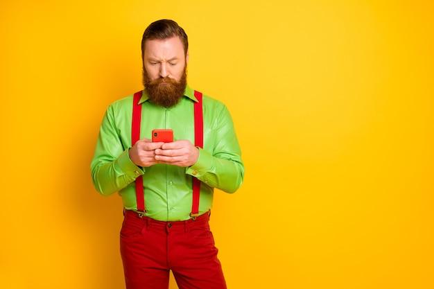 Ritratto di uomo pensieroso mentalità usa smartphone leggere informazioni di social network confuso seguire app ripubblicare indossare un bell'aspetto pantaloni pantaloni isolati colore brillante