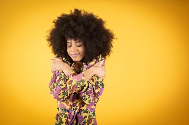 Il ritratto di una donna dalla pelle scura afro mista, con gli occhi chiusi e abbracciati